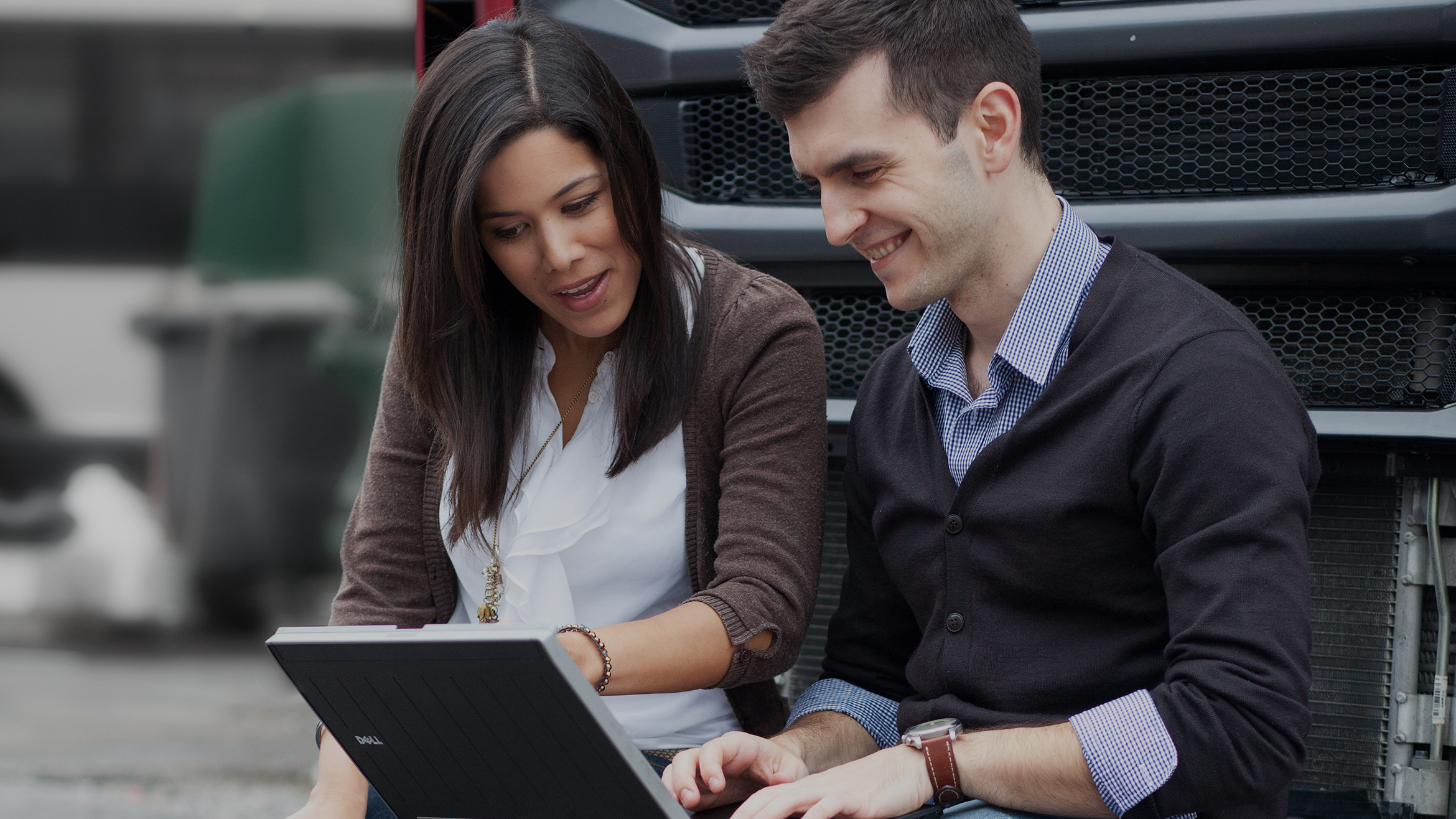 Two employees leaning against a truck looking at a laptop