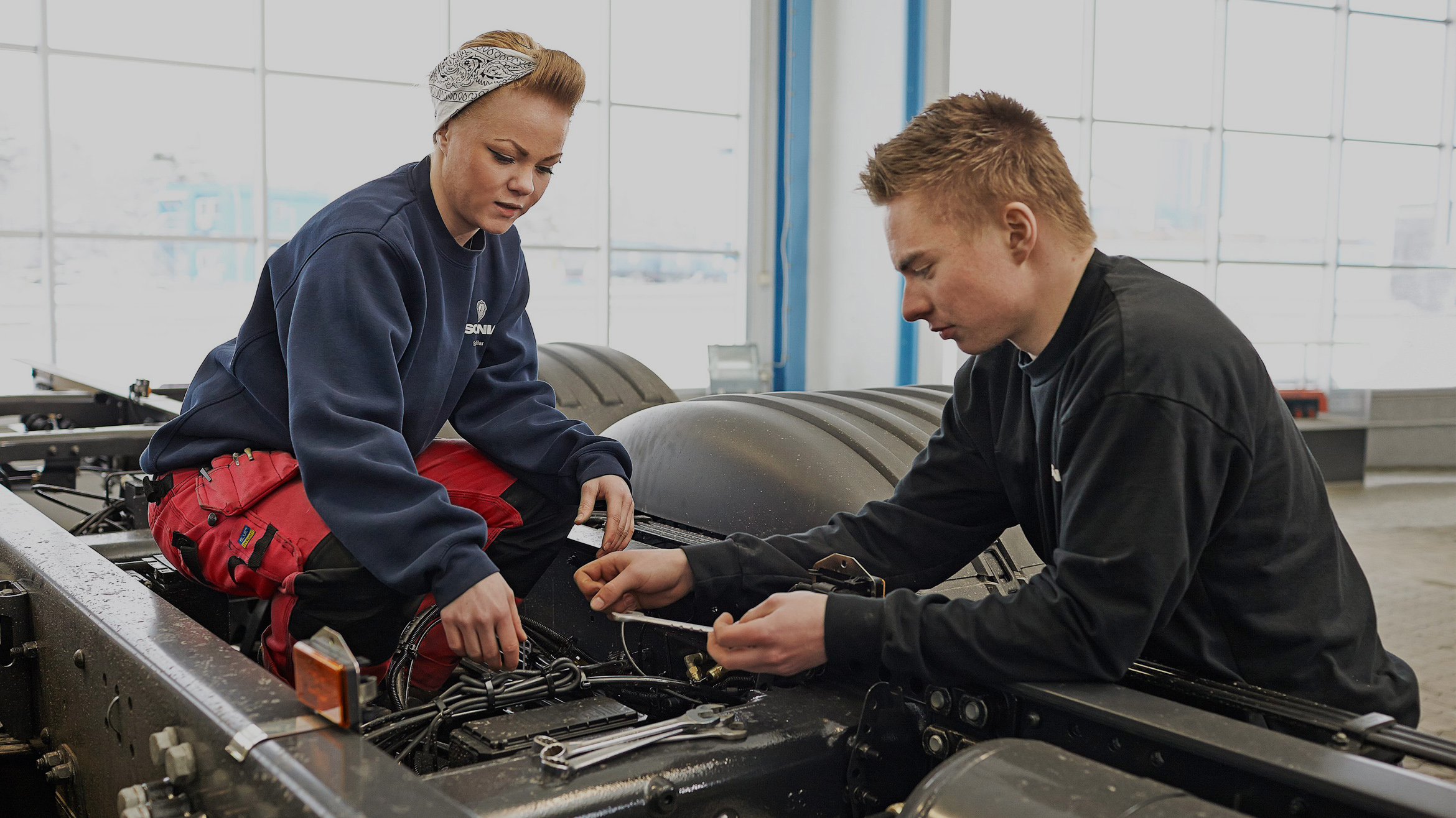 Two engineers working on a Scania truck