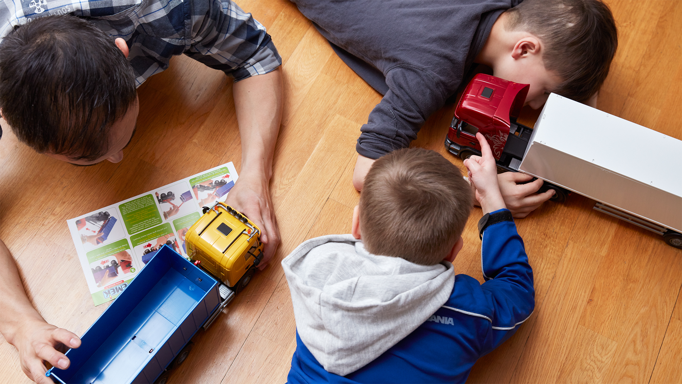A family playing with model trucks