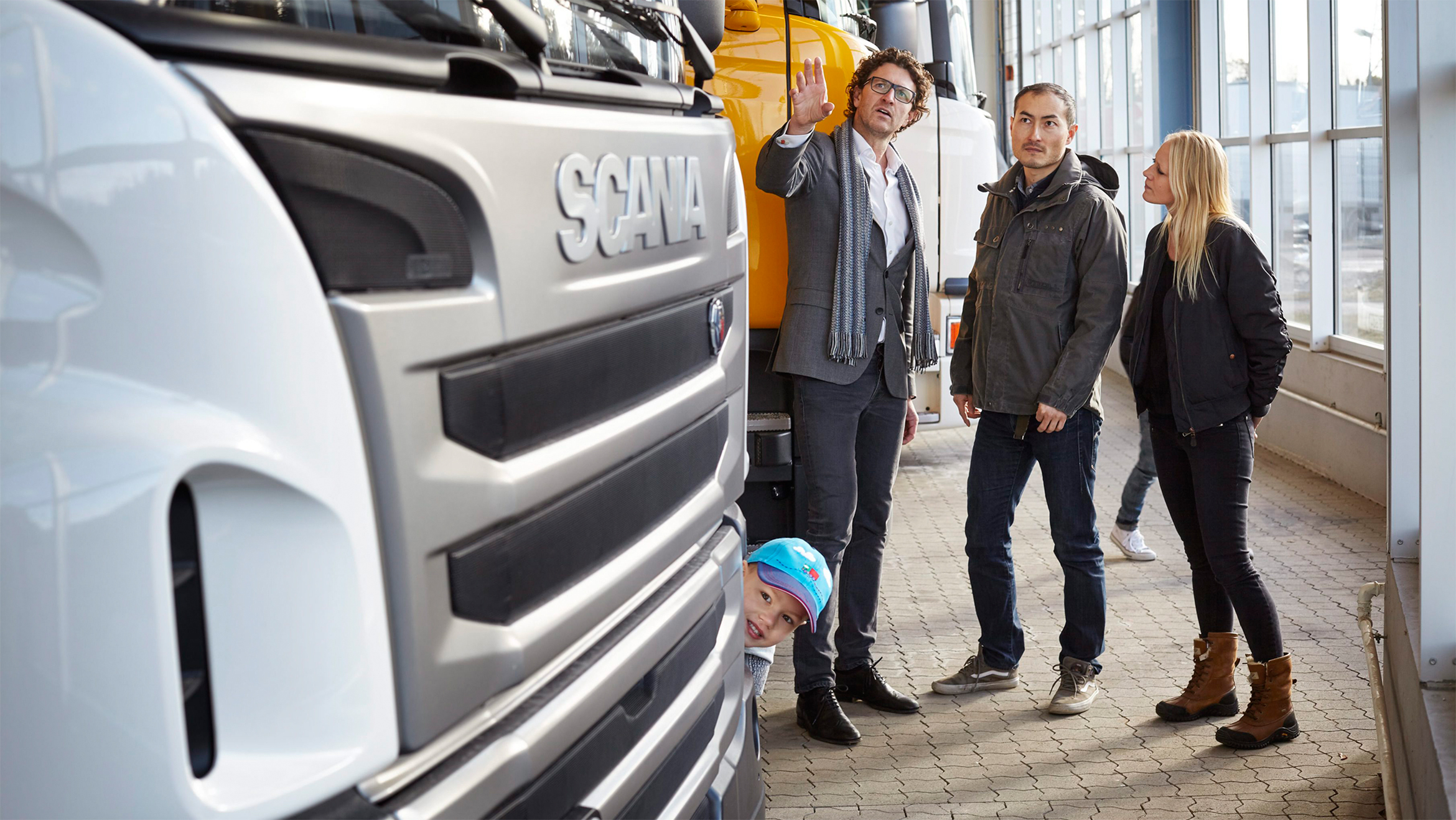 A couple talking to a member of Scania staff inside a dealership