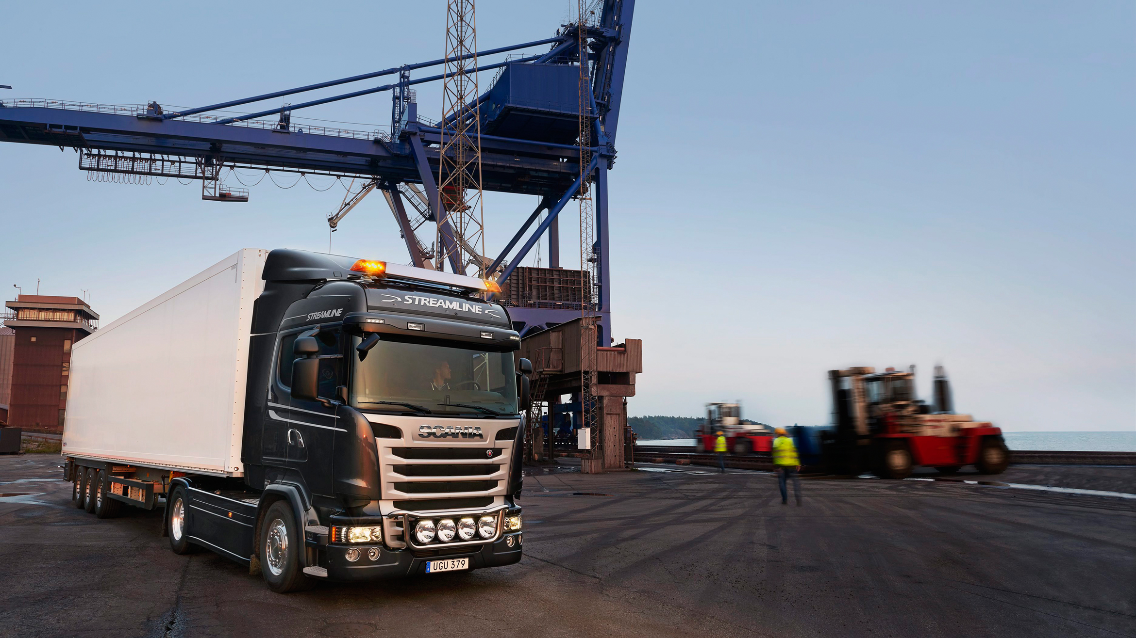 A Scania truck in front of a large crane by the sea