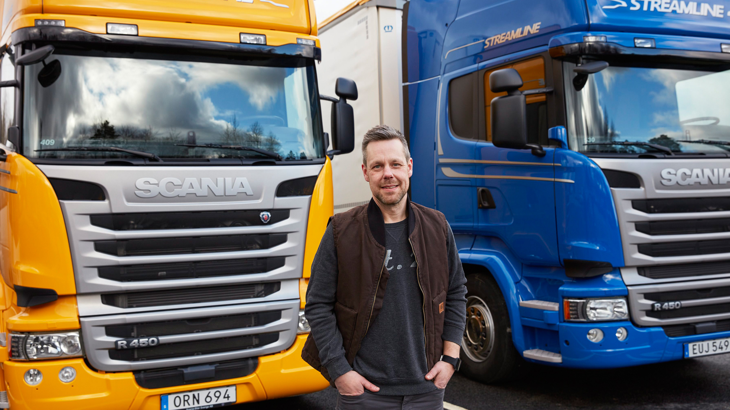 A driver standing between two Scania trucks