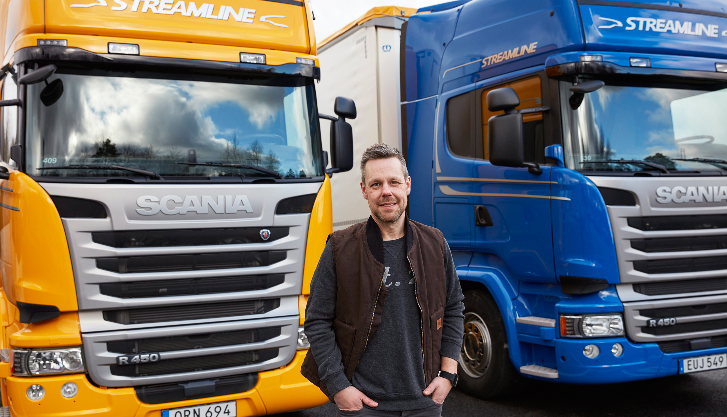 A man standing in front of two Scania trucks